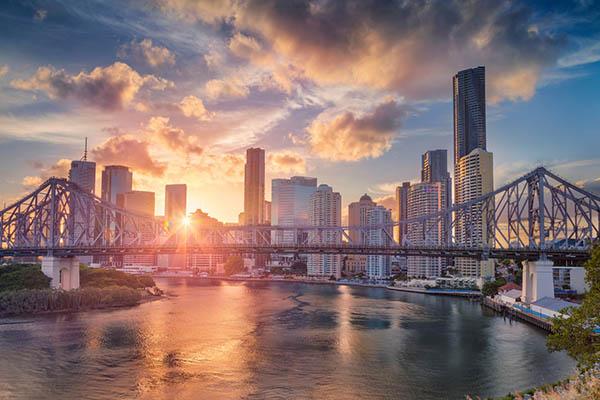 Cityscape image of Brisbane skyline, Australia with Story Bridge during dramatic sunset.