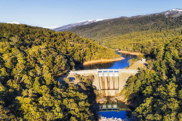 Snowy river in Snowy mountains of national park in Australia blocked by a concrete dam to generate electricity. Remote evergreen forests covering slopes of high mountains with snow tops.